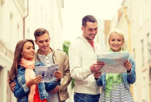 34811772 - travel, vacation and friendship concept - group of smiling friends with city guide and map exploring city